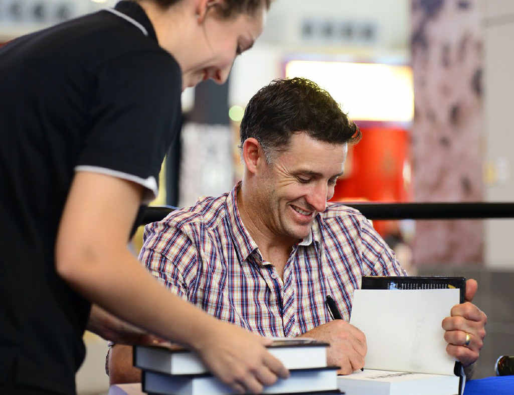 Michael Hussey signs copies of his autobiography for Ipswich fans.
