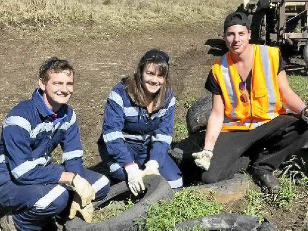HELPING HANDS: Dirty Gloves volunteers Matt Baker, Simona Borra and Michael Favel help clean up Sid Plant's property near Oakey. The Queensland Murray-Darling Committee volunteer program wraps up soon.