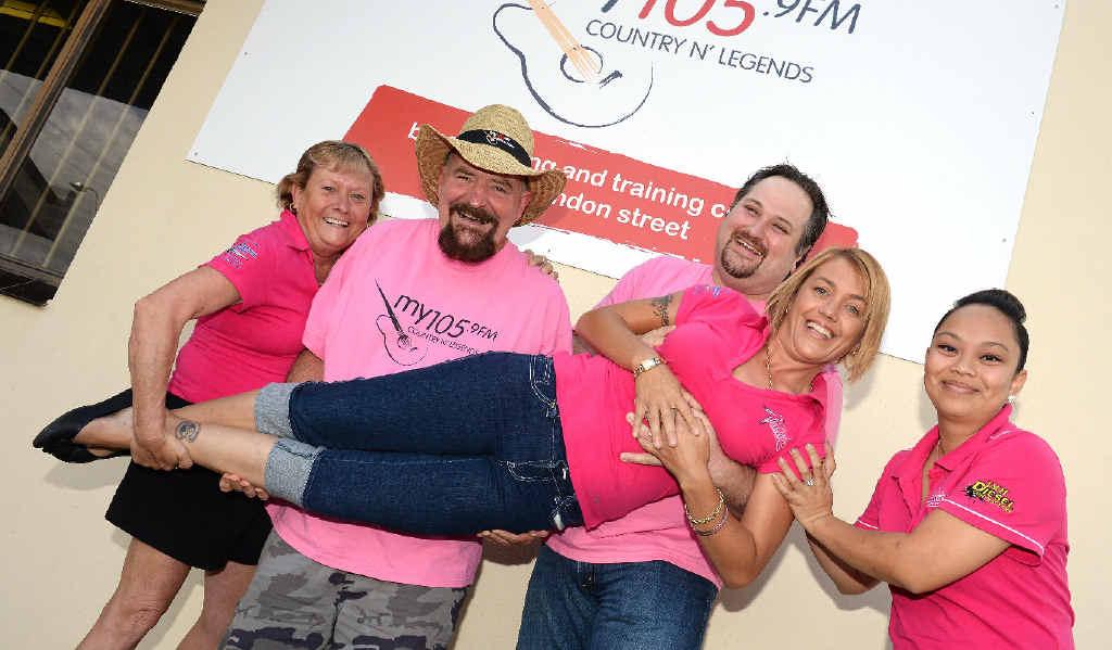 Vicki Vidier, Neil Macca, Daniel Webster and Monica Fletcher lift Raelene Wells in support of Pink Ribbon Charity.