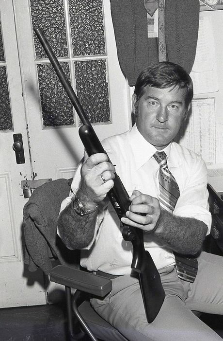 Brian Tighe with the 0.22 calibre rifle used by the robber.