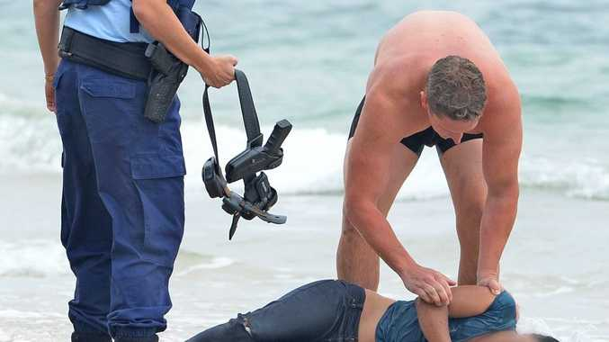 A Tweed police officer saving a woman in the surf.