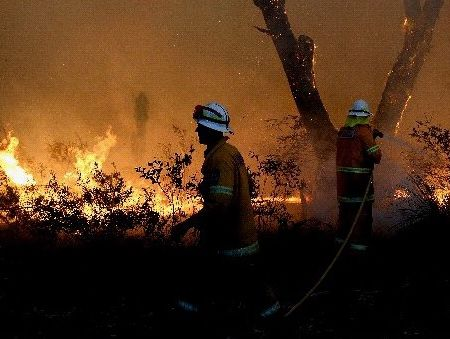 Rural Fire Service volunteers retreat after unsuccessfully trying to save a house from a bushfire at Dargan, east north of Lithgow