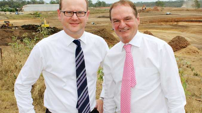 Daniel Brekan General Manager Queensland for Goodman Group and Ipswich Mayor Paul Pisasale stand on Montgomery Street, Redbank with earthworks underway for the new Redbank Motorway Estate in the background.