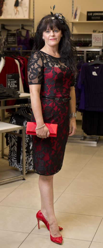 Nicci Richards wears a red shift dress with lace overlay.