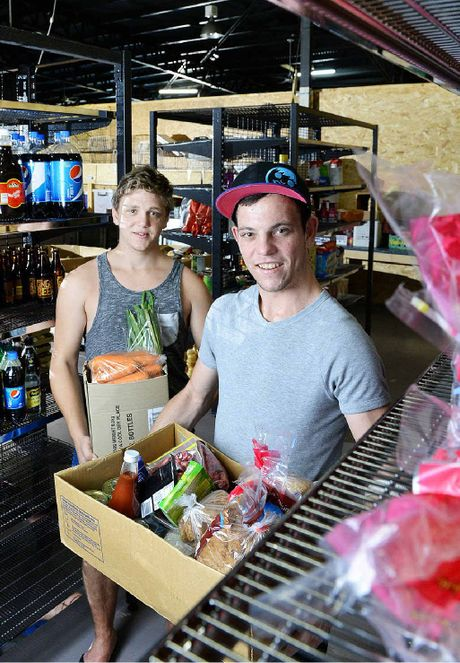 HELPING HANDS: Cameron Nichol and Ben Kimber from the Ipswich Food Barn enjoy the organised nature of the premises with new shelves purchased with a grant.