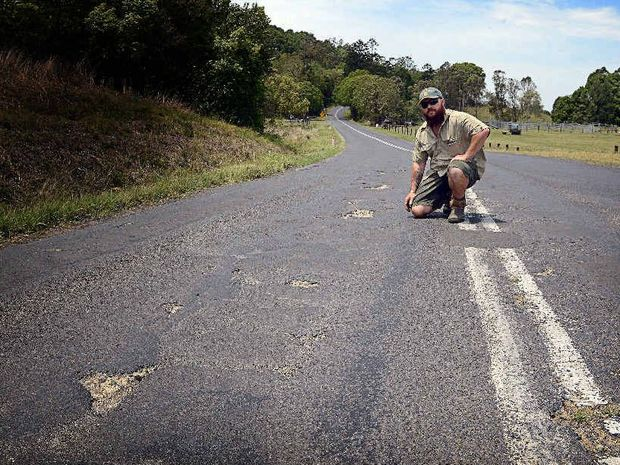 SORRY STATE: Peter Szaak of Booerie Creek is concerned about the condition of Nimbin Rd in front of his house, where there have been eight accidents in six months.