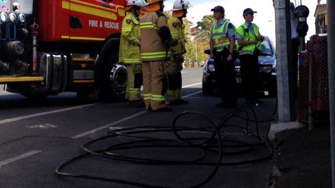 Police and firefighters investigate a fallen powerline in front of Toowoomba Army Disposals in Ruthven St.