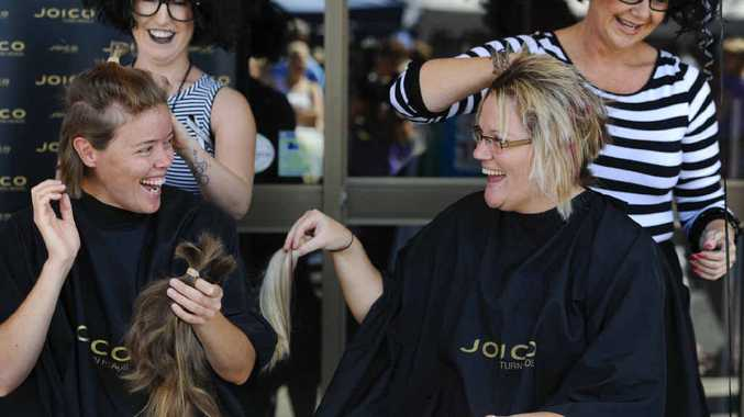 MAKING THE CUT: Emma Thrum and sister-in-law BJ Creed have their locks chopped for cancer research. Photo: JoJo Newby