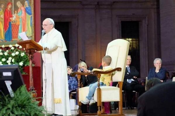 The little boy takes a seat in the Pope's chair.