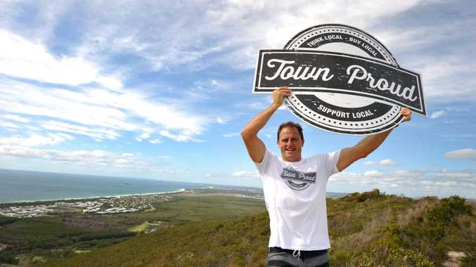 Rugby League legend and Mooloolaba business owner Billy Moore shows his support to APN's Town Proud campaign, holding the Town Proud logo on top of Mt Coolum. Photo: Iain Curry / Sunshine Coast Daily