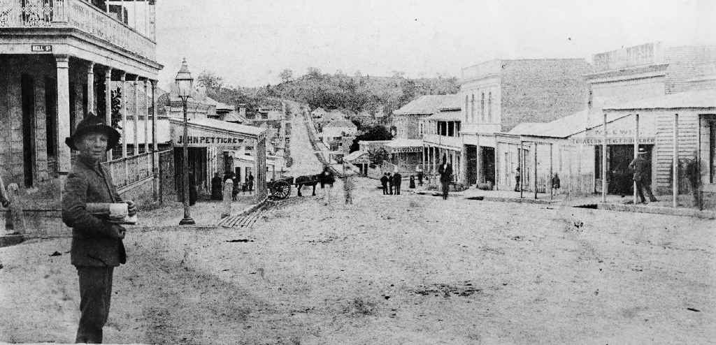 An 1883 image of Ipswich looking down Brisbane Street from the corner of Bell St. The Bank of New South Wales building is on the left, behind the unidentified boy.