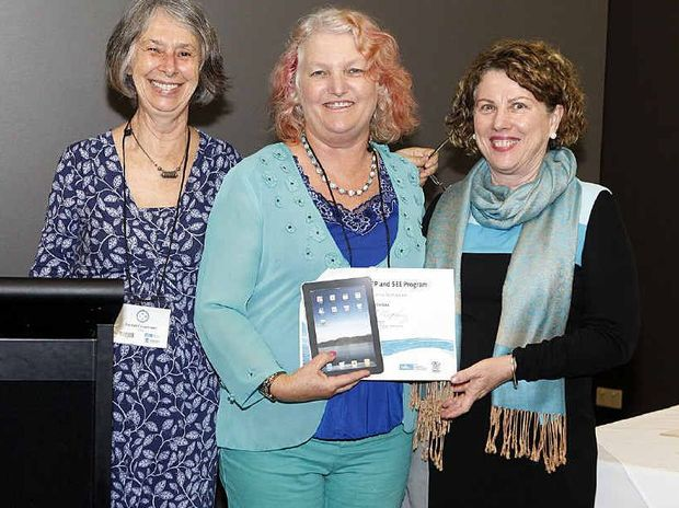Senior education consultant Carmel Carstensen (left) and TELLS director Helen Murphy (right) present Tina Stritzke with her award.