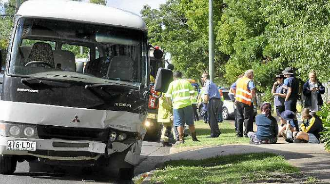 BUS CRASH: School students are checked over by paramedics after a bus and car collided in East Toowoomba yesterday.