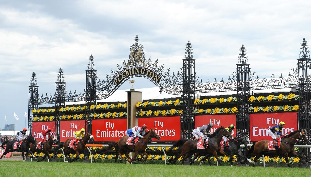 Emirates Melbourne Cup field pass the winning post with one lap remaining during 2012 Melbourne Cup Day