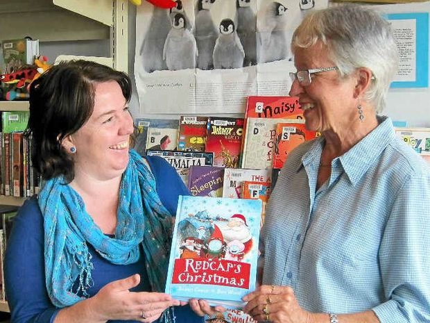 CHRISTMAS GIFT: Author Sue Cason (right) presents Redcap's Christmas to Clarence Library's Angela Clarke. Photo: contributed