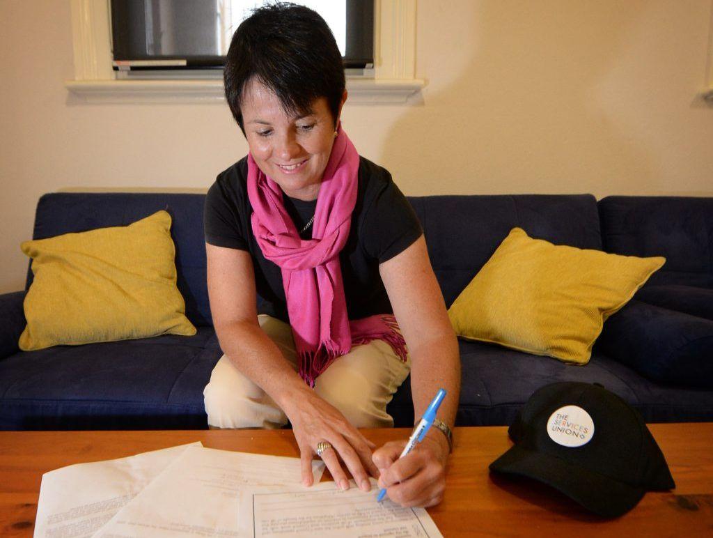 Kay Becker signing a no redundancies pledge for council workers after de-amalgamation. Photo Allan Reinikka / The Morning Bulletin