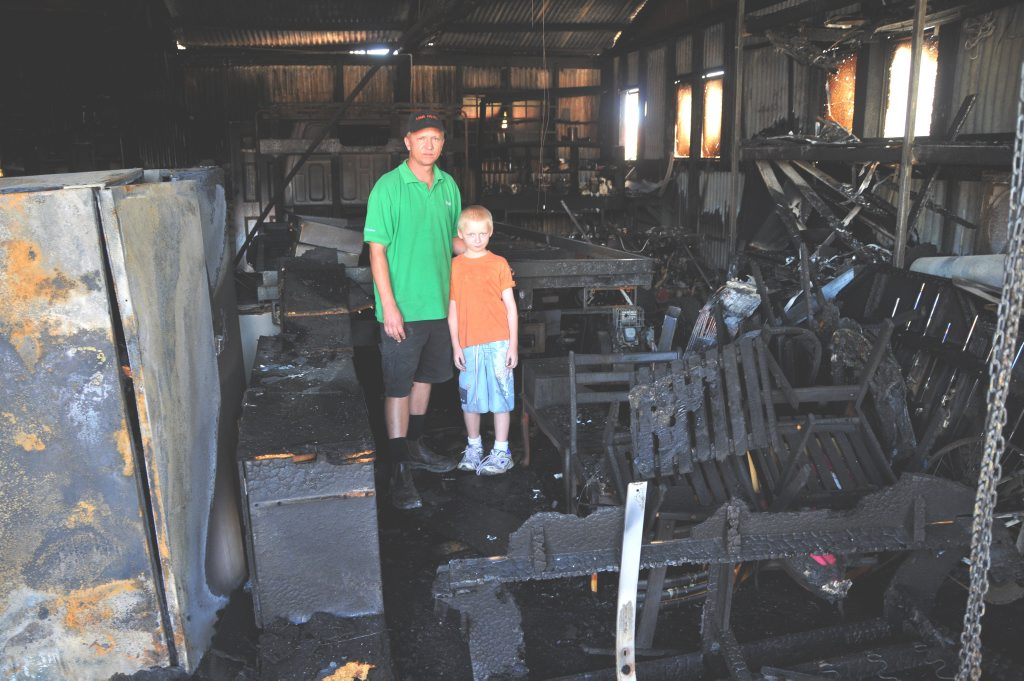 William Roberts and son Luke, 9, stand amid the rubble of their Clifton home and burgeoning second-hand business which was razed in a Tuesday night blaze.