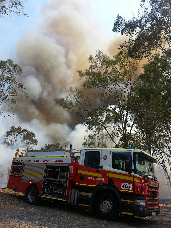 A fire crew at the scene of a large grass fire burning near High Street in Bundamba.