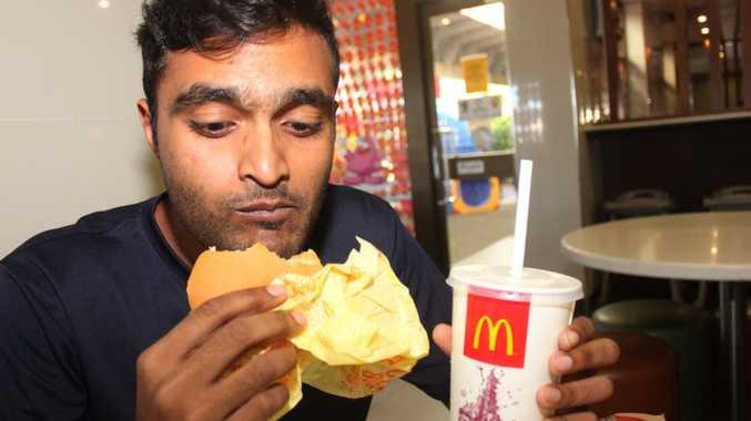 Singapore Airforce Pilot Naresh Balakrishnan, 23, tucks into his second burger at McDonald's. Photo: Austin King / The Morning Bulletin