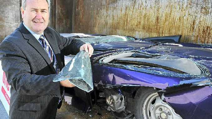 HOONS SQUEEZED: Police Minister Jack Dempsey looks at a crushed vehicle at the announcement of new legislation designed to give Queensland the toughest anti-hooning legislation in the country.