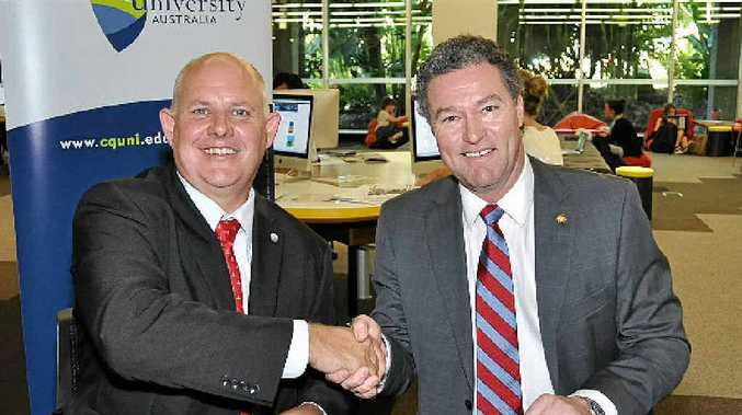 GROUNDBREAKING: CQ University Vice-Chancellor Scott Bowman and Education Minister John-Paul Langbroek finalise the paperwork, opening the door for the merger.