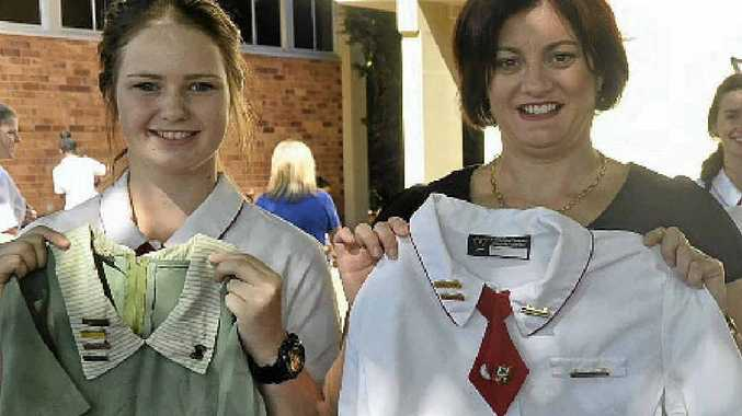 MEMORIES: Student Meagan Bradley and past student Madonna Sleba hold some old uniforms found in the time capsule.