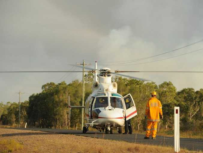 A firefighter guides the pilot of a helicopter to land on the Boonooroo Road to pick up a fire supervisor to monitor the blaze from the air.
