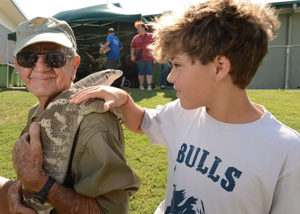 Calum de Mezieres with Bob Irwin and a four-year-old Spencers monitor at the annual Scales and Tails Festival at North Ipswich Reserve on Saturday.