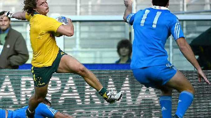 STEPPING UP: Wallabies winger Nick Cummins slices through the Italian defence on his way to the try line.