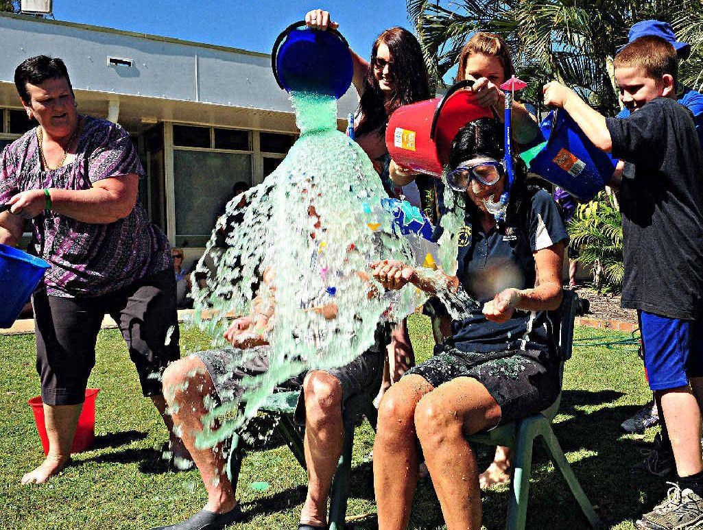 SLIME TIME: Bundaberg Special School teachers Brett Honke and Tanya Groves get slimed by staff and students.