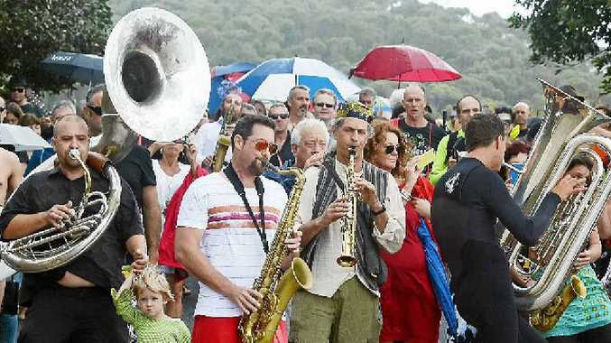 MEMORIAL SERVICE: Byron Bay icon, jazz musician/surfer Dave Ades, was farewelled at The Pass with a service (above) and a paddle out (right) to scatter his ashes.