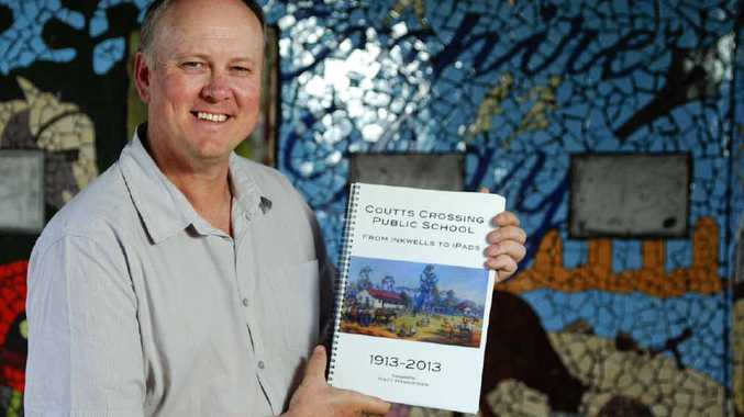 THROUGH THE DECADES: Coutts Crossing Public School principal Matt Hankinson with From Inkwells to iPads, a book he compiled on the school's 100-year history. PHOTO: JOJO NEWBY