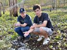 PELTED: Bradin Fogarty and Ben Holyoak beside the Bruce Hwy with some of the hail stones – some as big as tennis balls – 45 minutes after the storm hit.