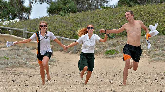 Pioneer State High School students Kate Whitehead (left), Bree Smith and Mitchell Cook head for the water at Mackay Harbour beach after finishing their final year of secondary school.