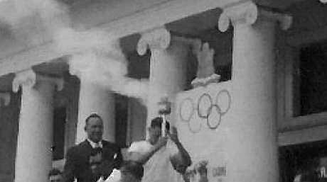 THE RELAY BEGINS: Con Verevis, from Cairns, sets out on the first leg of the 1956 Olympic torch relay.