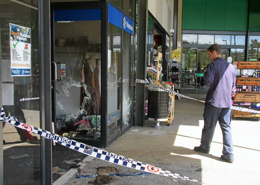TORCHED: Forensic crews sift through St Vinnies thrift shop in Fernvale after the blaze in 2010.