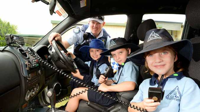 CALLING ALL CARS: Emily Tweedy, Jack Tweedy and Neisha Lauga with their Adopt-A-Cop Constable David Bletchly at The Hall State School.