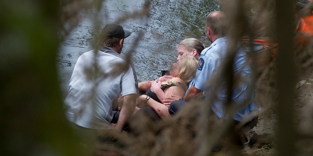 Police officers with the woman after she was taken to shore. Photo / Christine Cornege