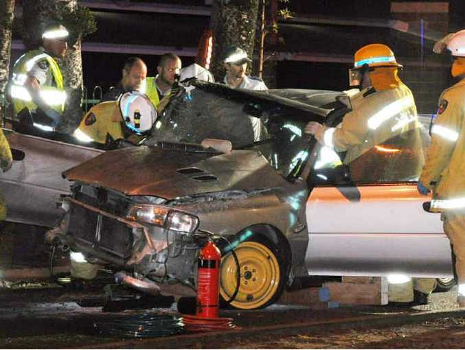 WRECKAGE: Firefighters and police officers clear the road after a car crashed outside The Strand Hotel, Yeppoon.