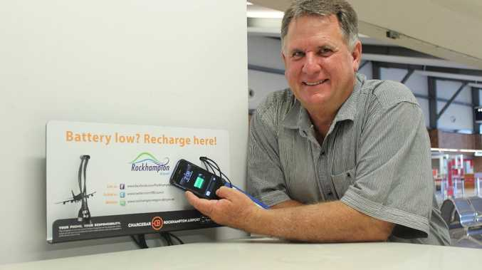 Cr Neil Fisher testing the new phone and tablet chargers at Rockhampton Airport.