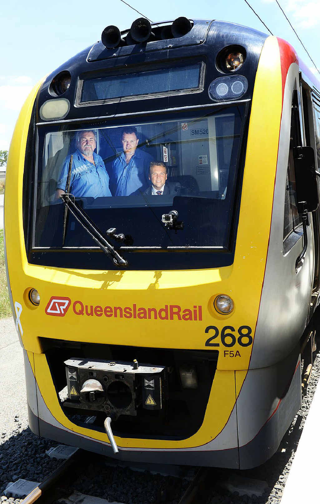 ALL ABOARD: QR trainers Peter Cherry and Troy Prebble with Minister for Transport and Main Roads Scott Emerson on board the first train to Springfield Central on Wednesday.