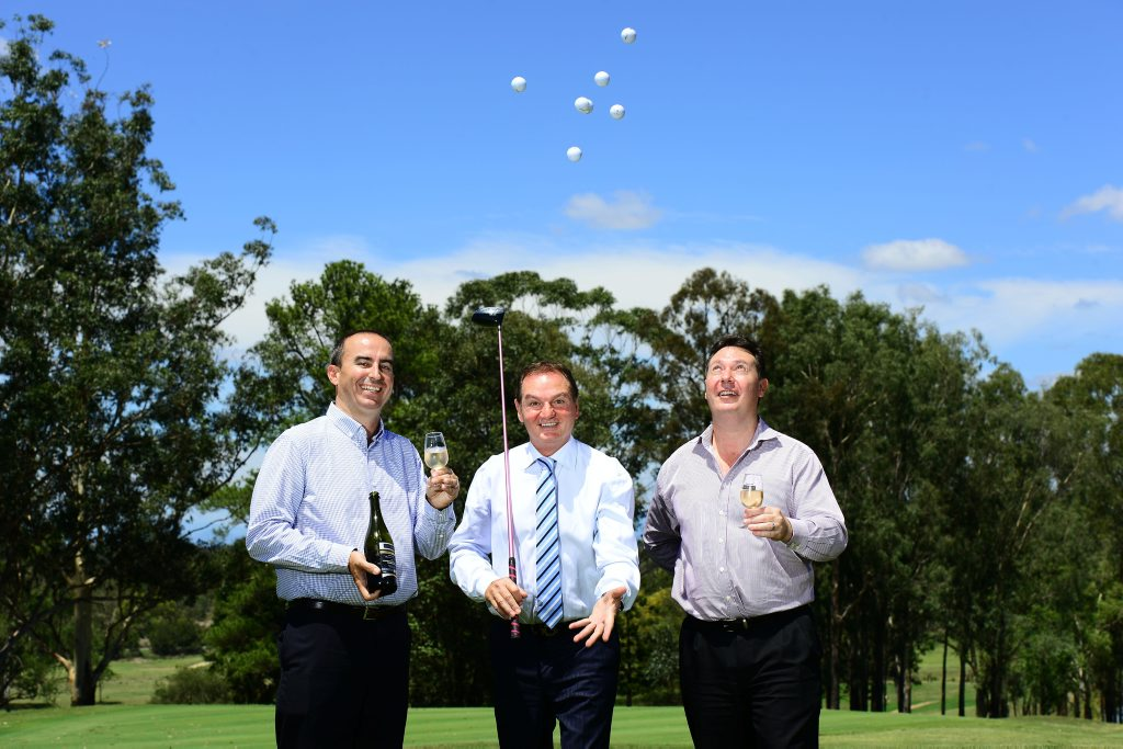 HERE'S CHEERS: Dean Merrell (left) and Rod Hill (right) of Sirromet Wines celebrate their acquisition of the Ipswich Golf Club with Mayor Paul Pisasale with a bottle of Sirromet champagne.
