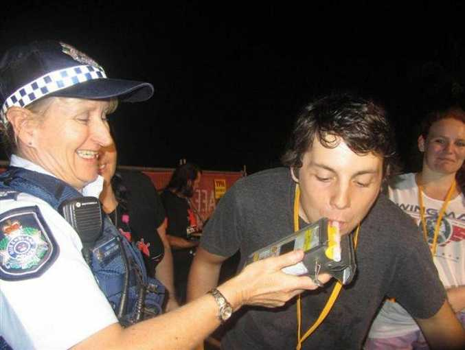 Constable Jennifer Henry with schoolies at Yeppoon this week as they line up to enter the Blow Zero competition.