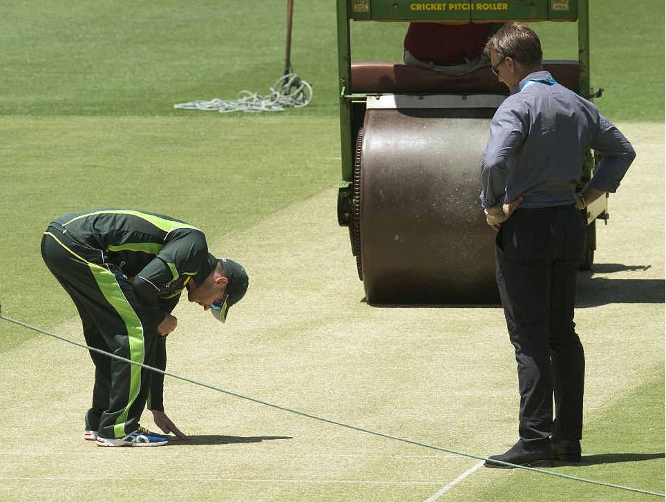 PITCH PERFECT?: National selector Andy Bichel watches on as Australian captain Michael Clarke checks out the Gabba wicket on the eve of today's first Test.