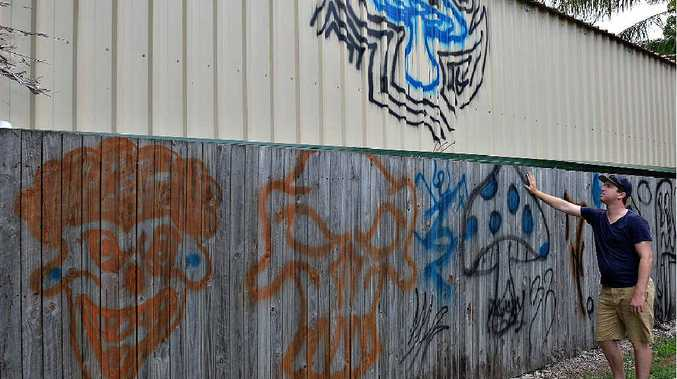 SUBURBAN VANDALISM: Michael Jones is disgusted by the graffiti painted on his father-in-law Frank Casey's back fence.