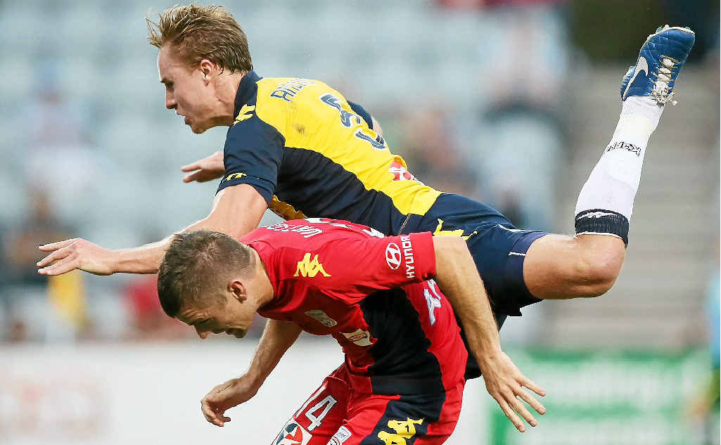 MAKING HIS PRESENCE FELT: Mariners defender Zac Anderson dives over Adelaide United midfielder Cameron Watson earlier this year.