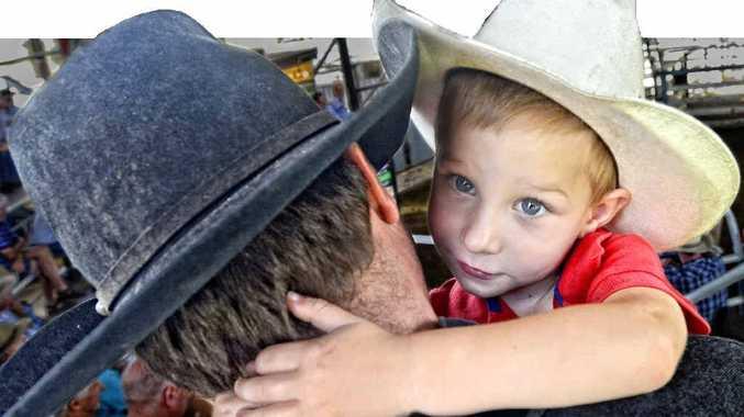 BIG DAY OUT: Hunter Ellem, 3, gives his dad Brett a hug at the Grafton saleyards last week. Photo Adam Hourigan