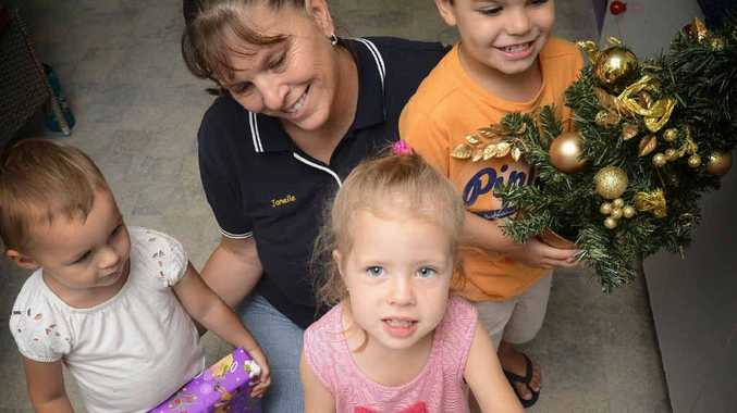 HELPING OTHERS: Education Leader at Cubby House For Kids Janelle Grory (back) with Olivia Lewis, Ella Darlington and Patrick Yuke hold presents for their 'giving tree' to go towards Christmas presents for the Bunya Childcare Centre in Winmalee. Photo: Adam Hourigan