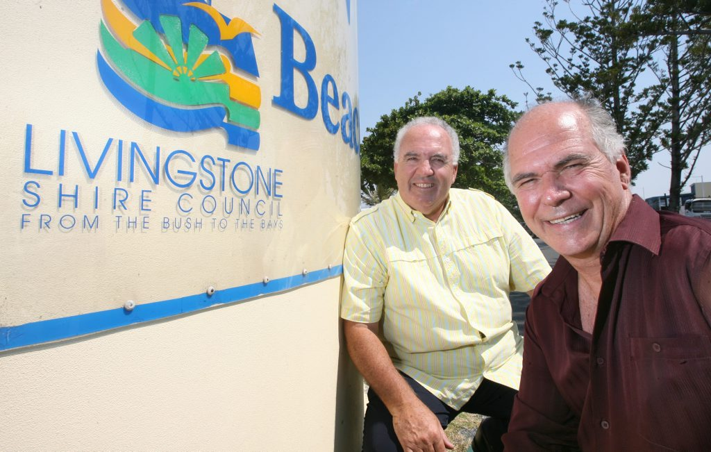 De-amalgamation advocates Paul Lancaster and Bill Ludwig beside an old Livingstone Shire Council sign on the Yeppoon Main Beach. Photo: Chris Ison / The Morning Bulletin