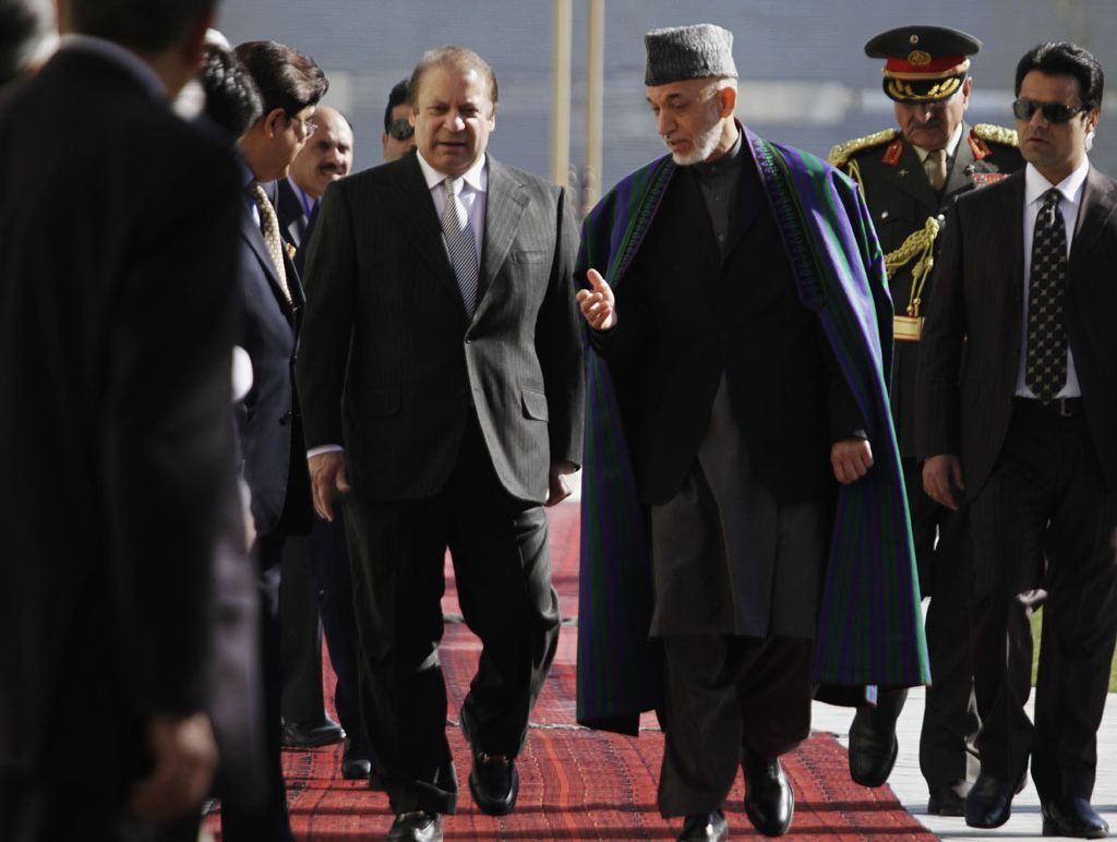 Afghan President Hamid Karzai, center right, talks with Pakistan's Prime Minister Nawaz Sharif while they inspect a guard of honor in Kabul, Afghanistan, Saturday, Nov, 2013. Sharif said Saturday that the recent release of a senior Taliban leader shows he is committed to helping bring peace to Afghanistan.